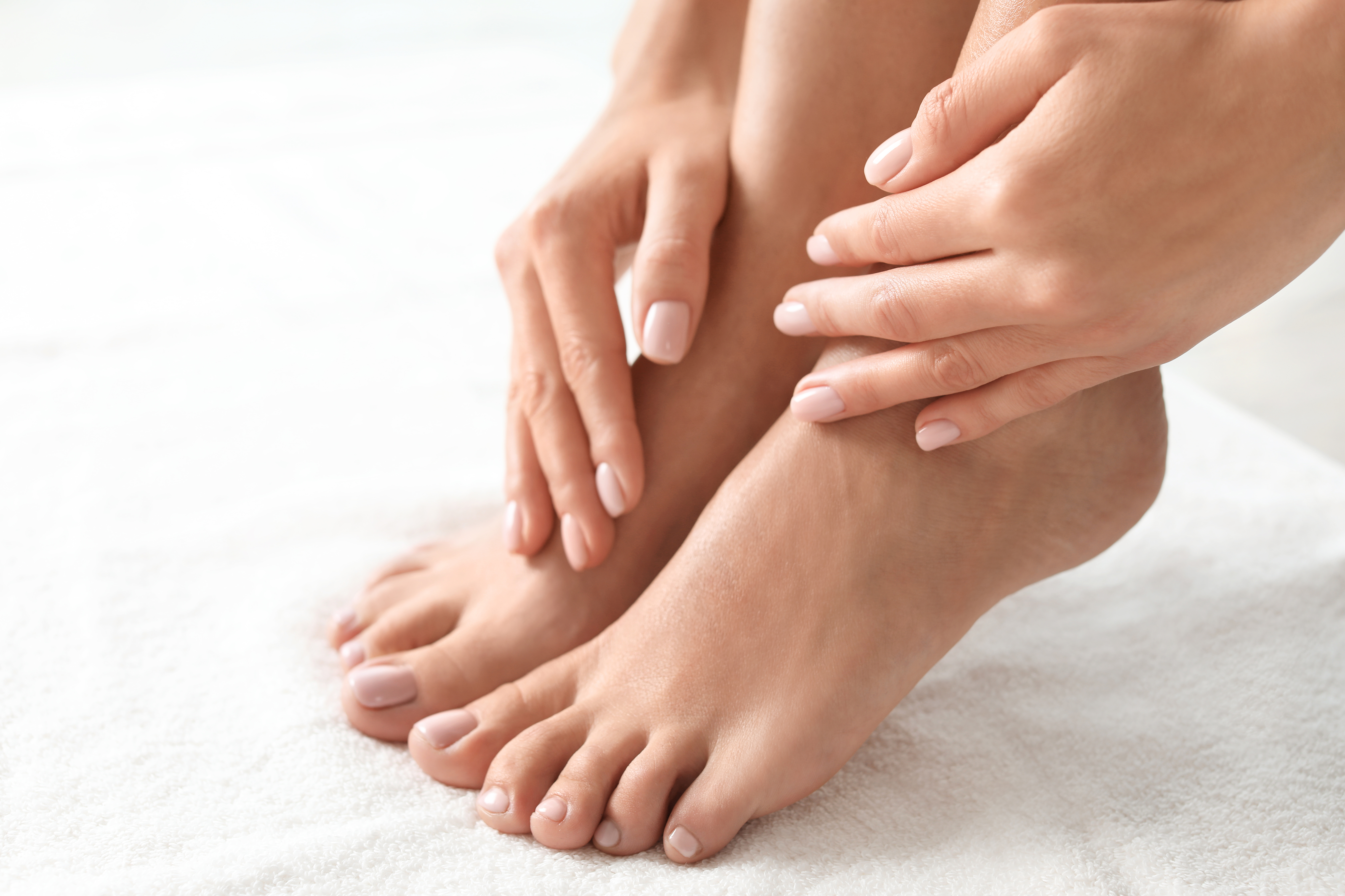 Woman with beautiful feet on white towel, closeup. Spa treatment