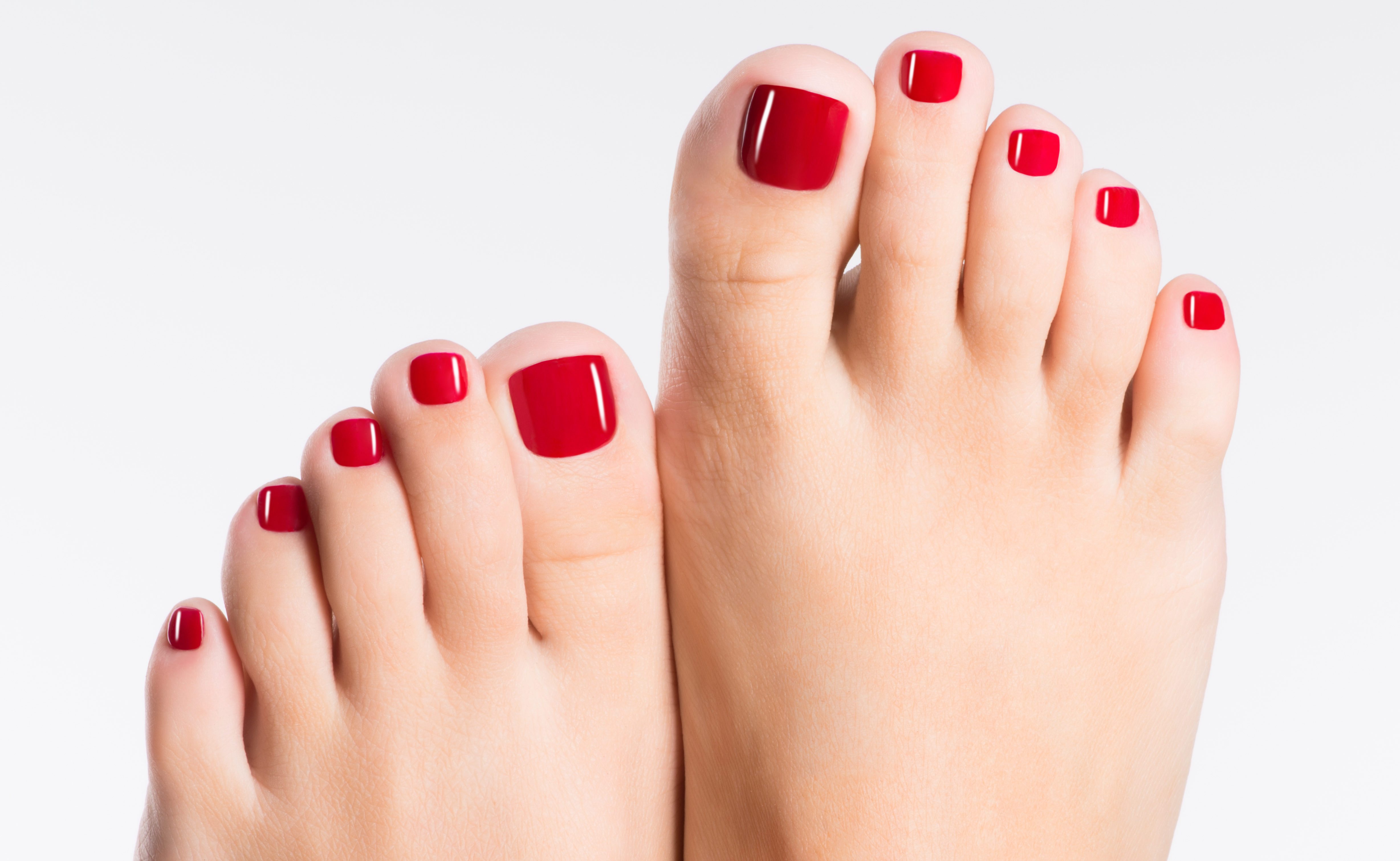 Closeup photo of a female feet with beautiful red pedicure over white background
